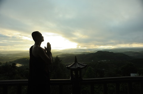 monk-holding-prayer-beads-across-mountain-2730217